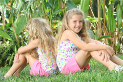 Twin sisters outside in grass. Shot of twin sisters outside in grass royalty free stock photo