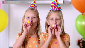 Twin sisters at a party. Blowing party horns stock video footage