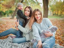 The twin sisters play with their children in the autumn park. Two beautiful young European girls, twin sisters play with their young children in the autumn park Stock Photo