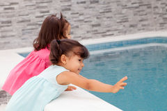 Twin sisters playing near the pool Stock Photo
