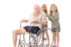 Twin sisters pushing eldery man. In wheelchair isolated on a white background Royalty Free Stock Images