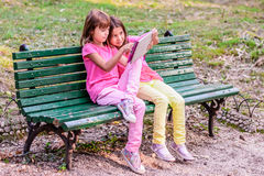 Twin sisters reading in the park. Twin sisters sitting on the bench and reading Stock Photo