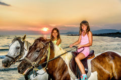 Twin sisters riding horses in the  sunset by the sea on the isla Stock Image