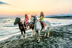 Twin sisters riding horses in the  sunset by the sea on the isla Royalty Free Stock Image