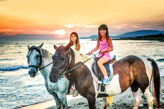 Twin sisters riding horses in the  sunset by the sea on the isla Royalty Free Stock Photos