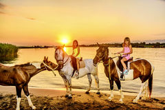 Twin sisters riding horses in the  sunset by the sea on the isla Stock Images