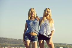 Twin sisters, girls, posing on blue sky. Twin sisters, girls or cute women, stylish female models, with long, blond hair in fashionable, knitted tops and shorts royalty free stock image