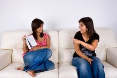 Twin sisters in sofa talking about a book stock photos