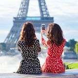 Twin sisters taking selfie near the Eiffel tower in Paris. Tourists enjoying their vacation in France. Romantic date or traveling couple concept Stock Photo