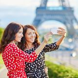 Twin sisters taking selfie near the Eiffel tower in Paris. Tourists enjoying their vacation in France. Romantic date or traveling couple concept Royalty Free Stock Photo