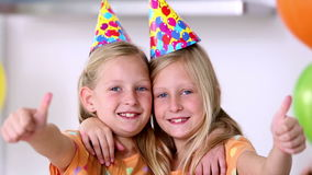 Twin sisters with thumbs up at birthday party Stock Photos