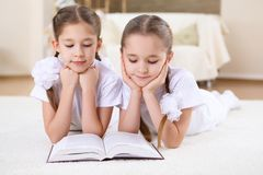 Twin sisters together at home with books Stock Image
