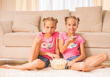 Twin sisters. Twins sisters are watching tv and eating popcorn sitting on the floor Stock Photos