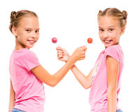 Twin sisters. Two happy little sisters with lollipops, on white background Royalty Free Stock Photography