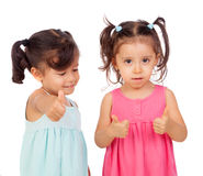 Twin sisters two years saying Ok. Isolated on a white background Stock Photo