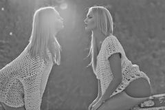 Twin sisters women. girls air kissing on sunny day. Twin sisters women, with long, blond hair, in fashionable, white sweaters air kissing on sunny day on natural stock image