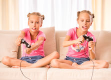 Twin sisters. Young twins are playing  video game holding joysticks in hands Royalty Free Stock Photo