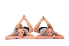 Twin sport girls lying on floor royalty free stock photos