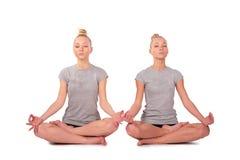 Twin sport girls meditating stock photography