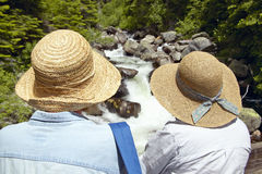 Twin straw hats, two women enjoy creek in Payette National Forest near McCall Idaho Stock Photography