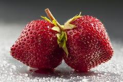Twin strawberries, studio shot, wet background, minimalist. Twin strawberries on grey and wet background in studio Stock Photo