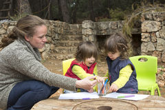 Twin toddler girls drawing on paper outdoor Royalty Free Stock Photography