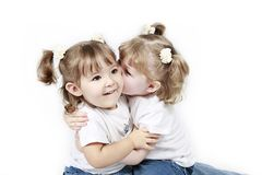 Twin toddlers kissing. Half body portrait of twin toddlers kissing, white studio background stock photo