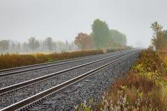 Twin Tracks Leading to Foggy Autumn Trees Royalty Free Stock Photo