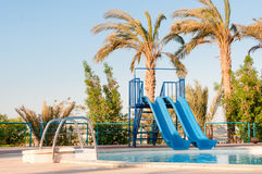 Twin water slides over the pool of a tropical luxury playground Royalty Free Stock Photography