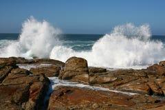 Twin waves splashing. Waves breaking against rocks and splashing Stock Photo