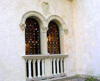 Twin Windows. Details of twin windows of southern mansion, Spanish architecture,white columns, and decorative arches, with unusual vertical spindles royalty free stock photography
