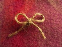 Twine bow centered on colorful Irish wool. Twine bow centered on fuchsia and magenta one hundred percent Irish wool scarf Royalty Free Stock Photos