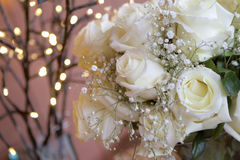 Twinkles and Roses. Bouquet of white roses and baby's breath against a backdrop of twinkle lights stock photos