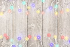 Twinkling Christmas lights double border on light gray wood. Twinkling Christmas lights double border, above view on a light gray wood background royalty free stock image