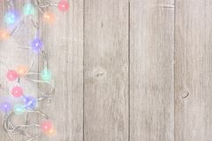 Twinkling Christmas lights side border on light gray wood. Twinkling Christmas lights side border, above view on a light gray wood background stock image