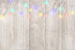 Twinkling Christmas lights top border on light gray wood. Twinkling Christmas lights top border, above view on a light gray wood background royalty free stock photography