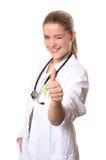 Twinkling femminile di medico, pollici su Immagine Stock