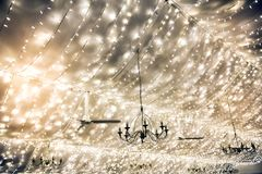 Twinkling party lights decorating a marquis roof. Twinkling party lights and chandeliers decorating a marquis ceiling in a wedding tent or at an event in a full royalty free stock image