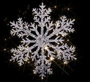 Twinkling snowflake. Artificial clear snowflake with lots of twinkling light effects in black back Royalty Free Stock Photo