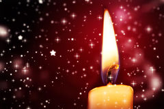 Twinkling stars against candle burning Stock Photography