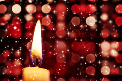 Twinkling stars against candle burning Stock Images