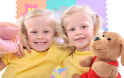 Twins. Smiling blonde twins girls playing Stock Photos