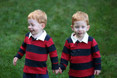 Twins. Twin baby boys holding hands outside Stock Photo