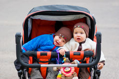 Twins. Cute twin boys outdoors in the stroller Stock Photo