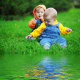 Twins. Cute twins babies sitting on fresh green grass in park Royalty Free Stock Photography