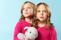 Twins. Portrait of two smart girls in crimson clothes against blue background Stock Photos
