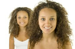 Twins. Smiling twins on white background. They're looking at camera. Focus on first person Stock Image
