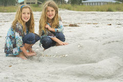 Twins with alligator sand castle Stock Photo