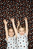 Twins with arms raised. Royalty Free Stock Images