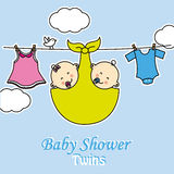 Twins baby shower. Baby girl and boy with clothes hanging on the rack Stock Image